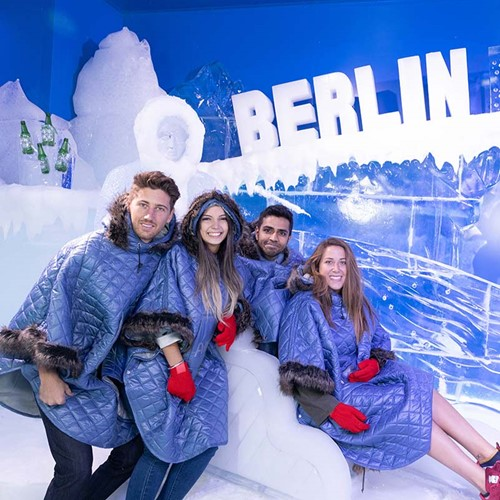 Four people posing on an ice sculpture at the Berlin Icebar.