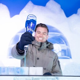 A bartender pouring drinks into glasses made of ice at the Berlin Icebar.
